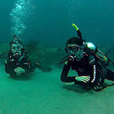 Two students in scuba gear crossing arms under water