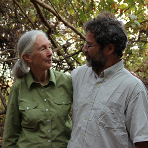 Michael Wilson wears a gray shirt and stands by Jane Goodall who wear a green shirt