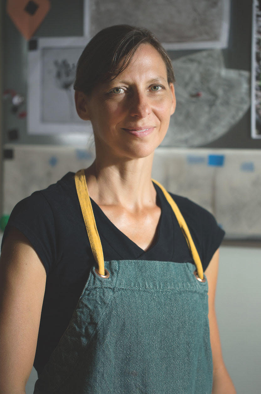 artist in residence Hargens stands in her studio with apron