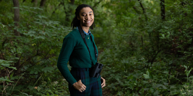 Simone Maddox stands in the woods with binoculars and looks for birds
