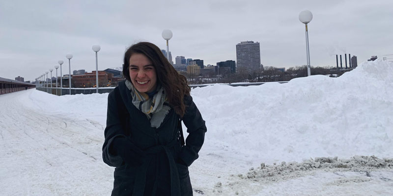 Alex Rich standing on the stone arch bridge in the winter