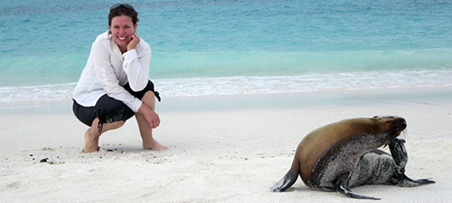 Professor Deena Wassenberg posing with sea lion on sandy beach in Galapagos Islands