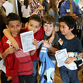 Four third-grade boys holding their poster passports at foundations of biology poster session
