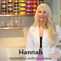 Photo of Hannah Folis, 2006 graduate, posing in front of cosmetic products