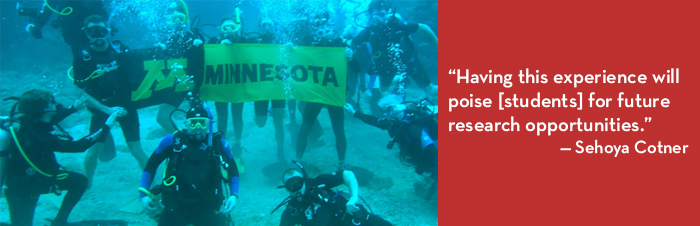 Photo of CBS students in scuba gear, underwater with U of M flag